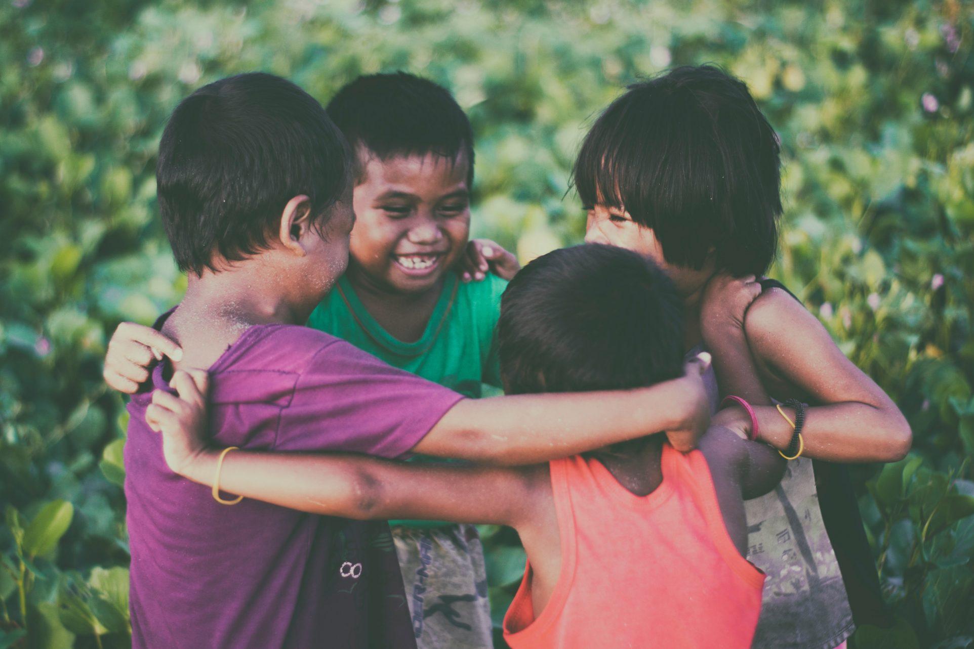 Hier ist eine fröhliche Gruppe Kinder, die sich im Kreis im Arm hält zu sehen