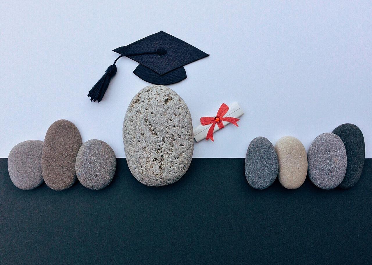 Das Bild Zeigt eine Graduierungsmütze einer Universität mit dekorativen Steinen aufgenommen