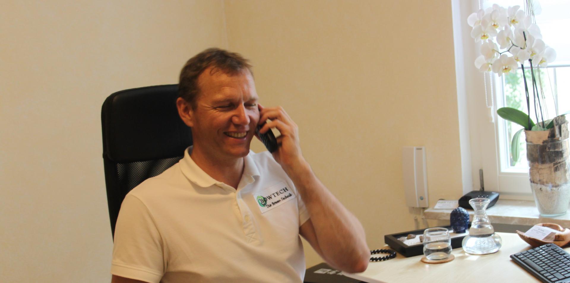 Das Bild zeigt Selfnessexperte aus Begeisterung. Gesundheitspraktiker Helmut RachlRachl im Büro bei der telefonischen Terminvereinbarung